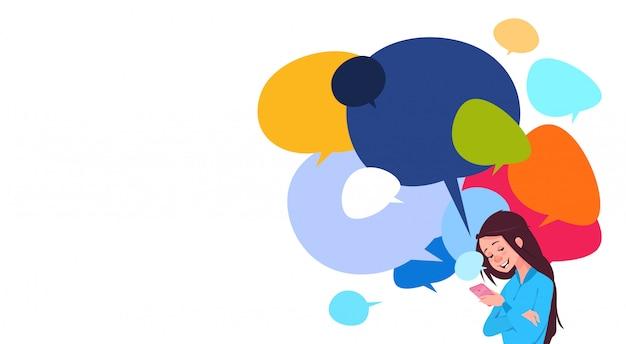 Jovem, menina, messaging, segurando, célula, esperto, telefones, sobre, coloridos, conversa, bolhas, fundo, social, mídia
