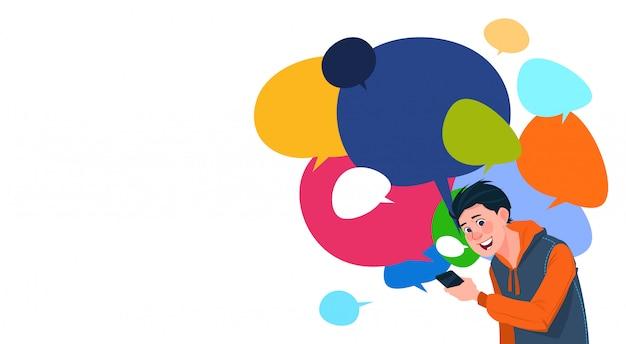 Jovem, menino, messaging, segurando, célula, esperto, telefones, sobre, colorido, bate-papo, bolhas, fundo