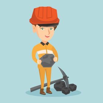 Jovem mineiro de capacete segurando um pedaço de carvão.