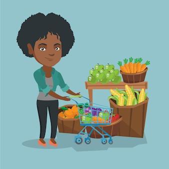 Jovem mulher africana empurrando um carrinho de supermercado.