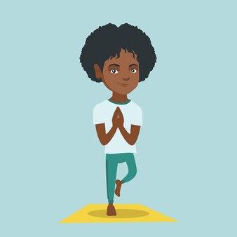 Jovem mulher africana praticando ioga pose de árvore.
