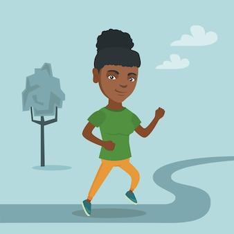 Jovem mulher afro-americana correndo no parque.