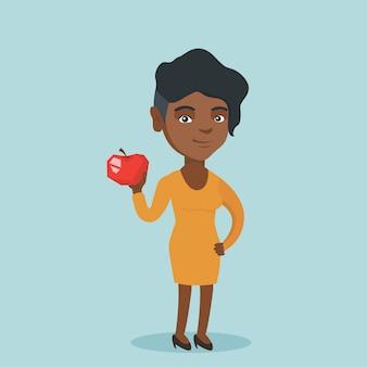 Jovem mulher afro-americana segurando uma maçã.