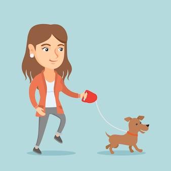 Jovem mulher caucasiana andando com seu cachorro.