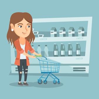 Jovem mulher caucasiana com um carrinho de supermercado.