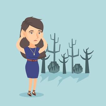 Jovem mulher caucasiana em pé em uma floresta morta.
