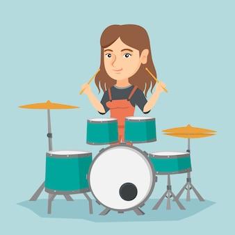 Jovem mulher caucasiana tocando o tambor.