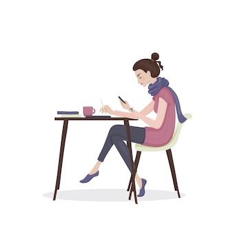 Jovem mulher com cabelos castanhos em uma roupa rosa e lenço roxo, sentado à mesa com uma xícara de chá e livros com telefone na mão. uma aluna.