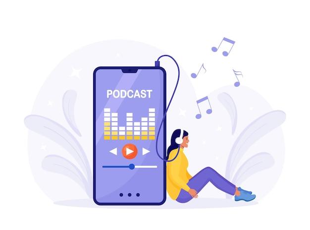 Jovem mulher com fones de ouvido, sentado no chão e transmitindo para podcast no smartphone. menina ouvindo rádio online com telefone celular. show de podcasting online, webinar, treinamento, podcast tutorial