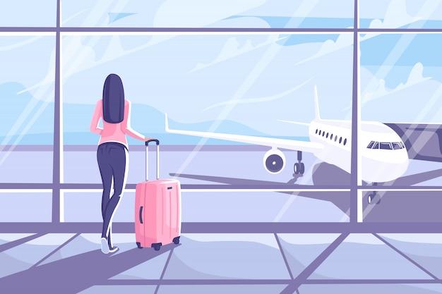 Jovem mulher com uma mala está de pé no terminal do aeroporto