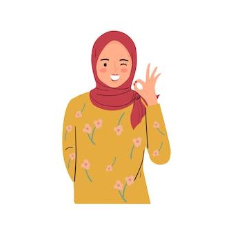 Jovem mulher está piscando, sorrindo e fazendo o sinal bem com gesto com a mão. moça bonita usar hijab.