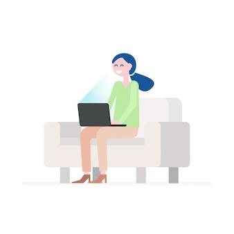 Jovem mulher feliz que senta-se no sofá confortável e que usa o portátil.