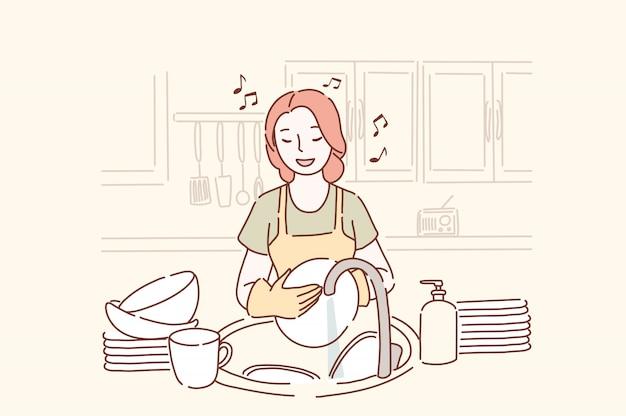 Jovem mulher lavando pratos e ouvindo música na cozinha de bom humor.