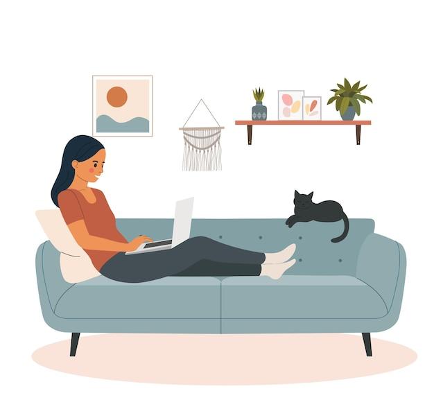 Jovem mulher olhando para um laptop e deitada no sofá da sala.