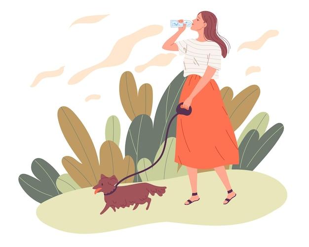 Jovem mulher passeando com o cachorro e bebendo água.