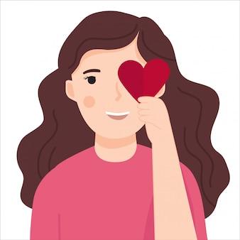 Jovem mulher segurando coração vermelho em forma de papel no olho dela