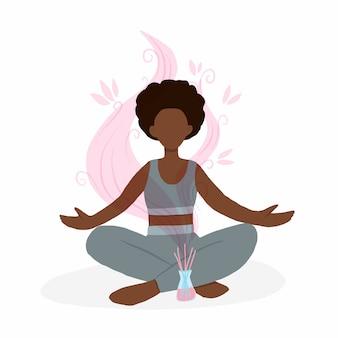 Jovem mulher sentada em pose de lótus com difusor de aroma.