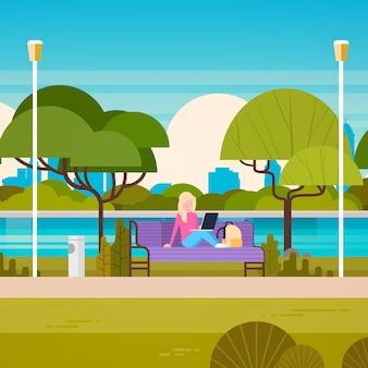 Jovem mulher sentada no banco no parque usando o computador portátil ao ar livre