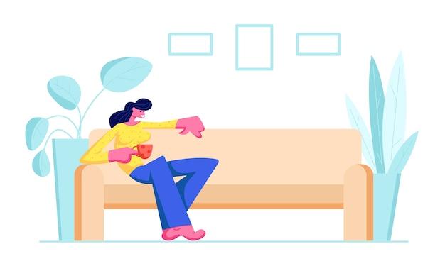 Jovem mulher sentada no sofá confortável com uma xícara de chá ou café na mão em casa.