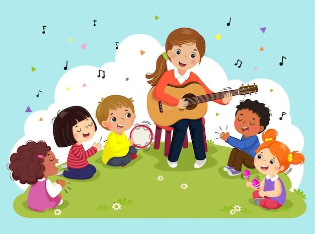 Jovem mulher tocando violão com um grupo de crianças cantando e tocando instrumentos musicais. professora e alunos tendo música no parque.