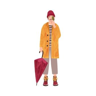Jovem na ilustração plana de capa de chuva. modelo masculino vestindo casaco amarelo e personagem de desenho animado de chapéu quente. cara sorridente segurando guarda-chuva e folha. humor de outono, pessoa aproveitando o tempo chuvoso.