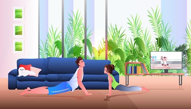 Jovem pai com filha fazendo exercícios de alongamento enquanto assiste a um programa de treinamento em vídeo on-line.