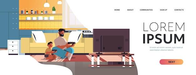 Jovem pai jogando videogame no console de videogame com o filho pequeno em casa.