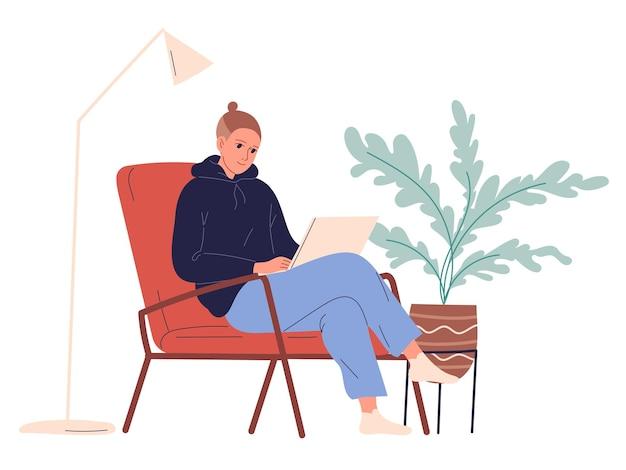 Jovem se senta em uma cadeira com um laptop.