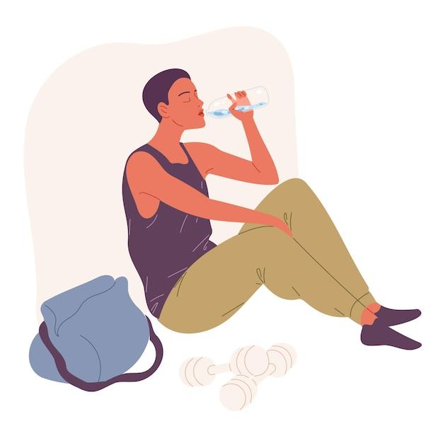 Jovem se senta no chão e bebe água.