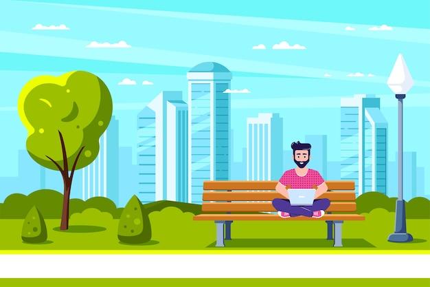 Jovem sentado no banco no parque e trabalhando com um laptop