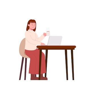Jovem trabalhando em uma mesa com laptop e tomando um café