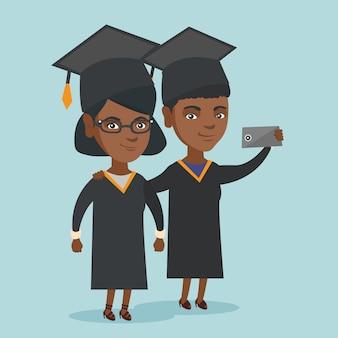 Jovens afro-americanos graduados fazendo selfie.