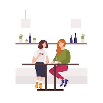 Jovens lindas sentadas no sofá de um café, bebendo café e conversando