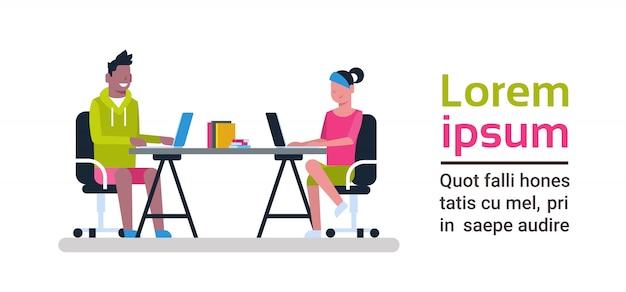 Jovens que trabalham nos computadores que sentam-se na mesa no conceito moderno do centro dos colegas de trabalho do espaço de coworking