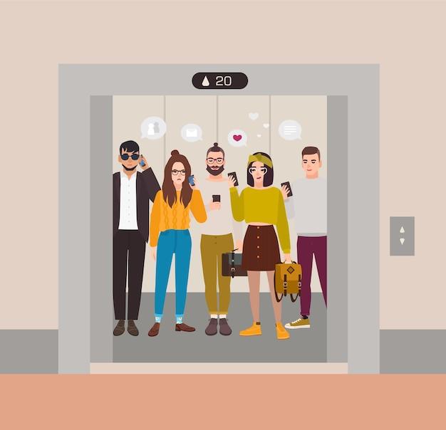 Jovens vestidos com roupas da moda em pé no elevador com portas abertas e usando smartphones