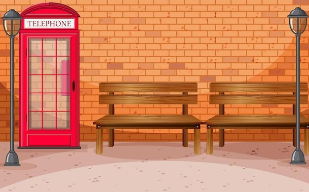 Lado da rua da parede de tijolos com caixa telefônica e banco
