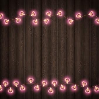 Lâmpada de forma de coração para decoração de lugar em fundo de madeira.