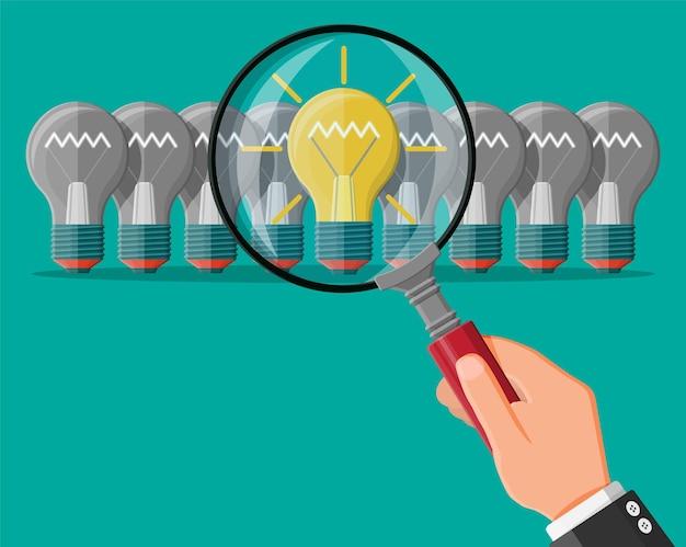 Lâmpada de ideia de luz brilhante sob a lupa. singularidade, individualidade, diferentemente destacando-se da multidão. criatividade, ideias, inspiração, motivação. arranque de negócios. ilustração vetorial plana
