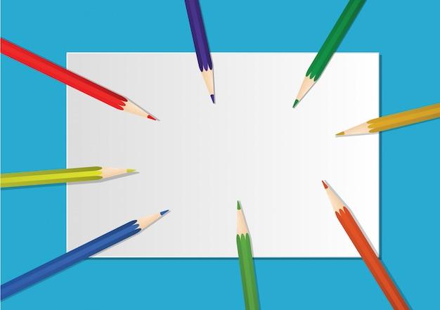 Lápis de cor são colocados em papel branco