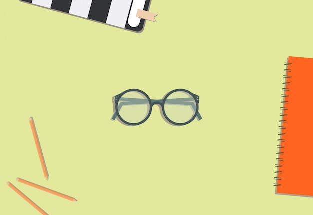 Lápis de óculos e livro com fundo creme