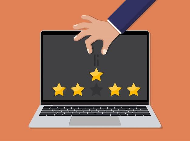 Laptop com mão jogando uma classificação por estrelas em um design plano. conceito de revisão do cliente