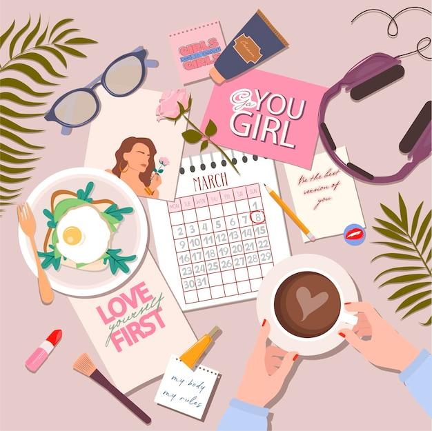Layout de negócios femininos. estilo de mesa plana leigos, mãos femininas segurar caneca com café, cartazes motivacionais com calendário de citações feministas para o mês de março, caneta, cosméticos, fones de ouvido, óculos e plantas.