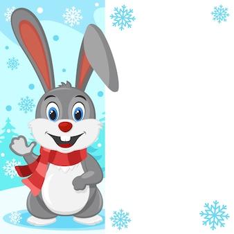 Lebre cinzenta em um lenço acenando com a pata em um fundo de inverno. lugar para texto.