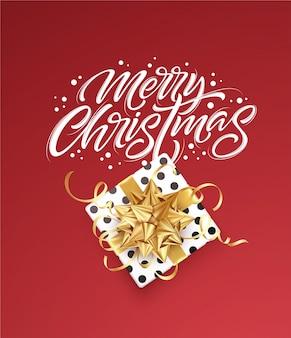 Letras brancas feliz natal em um fundo vermelho com uma caixa de presente e um laço dourado.