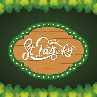 Letras de feliz dia de são patrício em moldura de madeira e ilustração de folhas de trevo