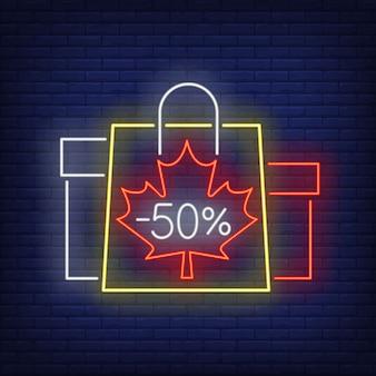 Letras de néon de cinquenta por cento menos com sacolas e caixas de compras