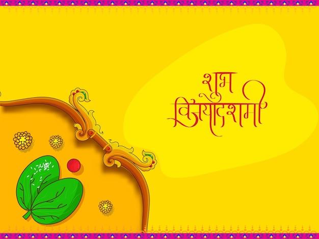 Letras hindi de shubh vijayadashmi (feliz dussehra) com arco, folha de apta e kumkuma no fundo amarelo.