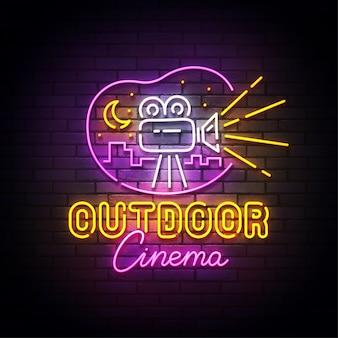 Letreiro de néon do cinema ao ar livre, cinema drive-in com carros em estacionamento ao ar livre