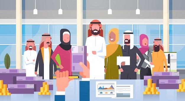 Líder de grupo de pessoas de negócios árabes dando salário em euro chefe mão segure dinheiro empresários equipe muçulmana