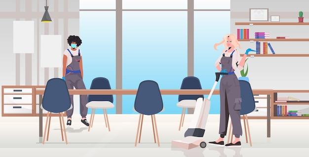 Limpeza profissional casal mistura corrida zeladores usando equipamento de limpeza trabalhando juntos interior do escritório horizontal